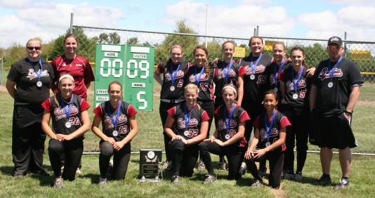 Moore (red) poses with her 14U team, the Northwest Bullets.
