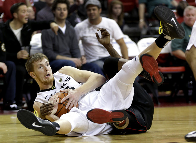 Oregon's E.J. Singler gets tangled up with Cincinnati's Cashmere Wright while grabbing a loose ball in the second half (AP Photo/Julie Jacobson)