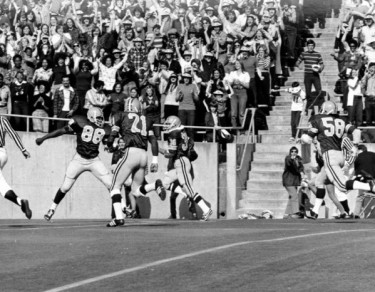 Black and white photo of two unidentified University of Oregon defenders closing in on an opposing quarterback during a game played at Autzen Stadium in the mid-1970s